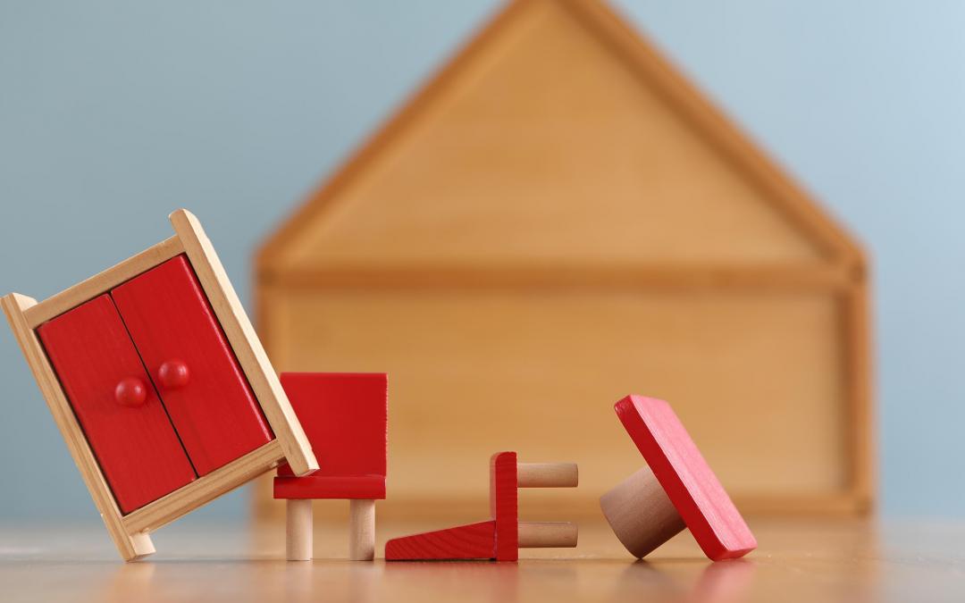 Hus i træ, med små legetøjs træmøbler foran. Indbosforsikring husforsikring